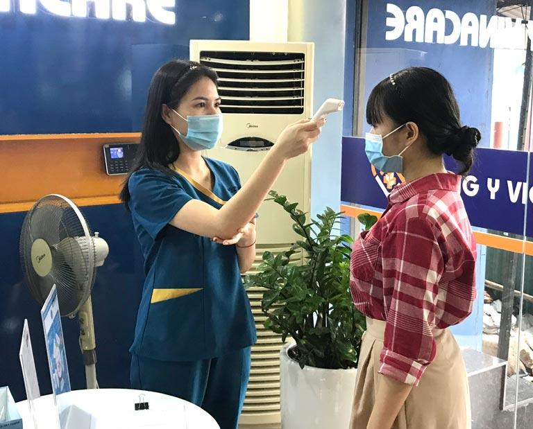 Khách hàng được đo thân nhiệt và sát khuẩn tay khi vào Viện